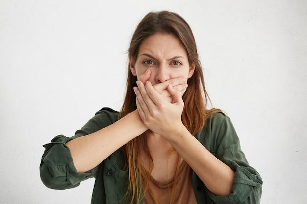 Mulher caucasiana, cobrindo a boca com as mãos, tentando manter o silêncio e não contar segredos de sua família. mulher jovem com aparência bonita gesticulando Foto gratuita