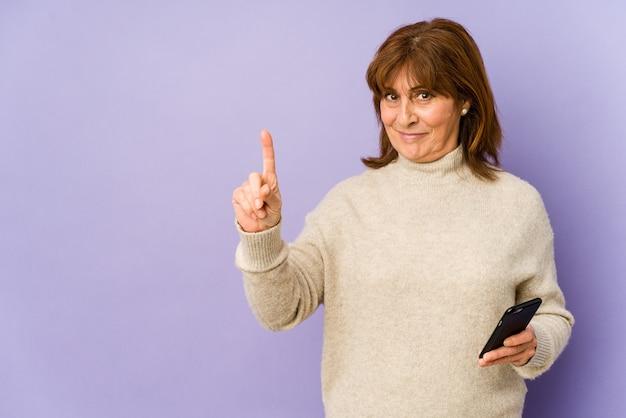 Mulher caucasiana de meia idade segurando um telefone mostrando o número um com o dedo. Foto Premium