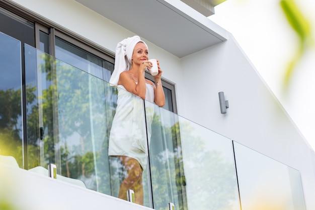 Mulher caucasiana depois do banho de toalha fica na varanda da villa e bebe café ou chá. um começo perfeito do dia. mulher calma e relaxada encontra o novo dia Foto gratuita