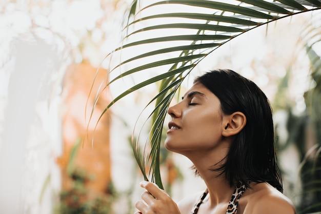 Mulher caucasiana feliz posando em um resort exótico. tiro ao ar livre de mulher alegre cheirando palmeira. Foto gratuita