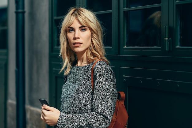 Mulher caucasiana jovem atraente olhando para o seu telefone inteligente ao ar livre Foto Premium