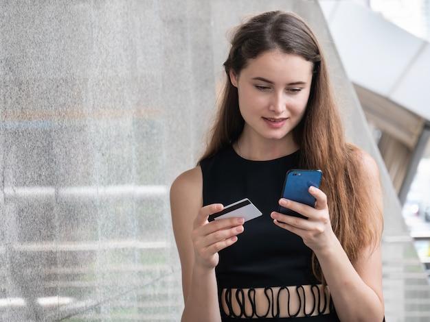 Mulher caucasiana, pagando on-line com cartão de crédito e telefone inteligente ao ar livre na cidade Foto Premium
