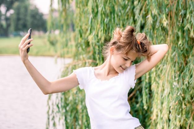 Mulher caucasiano loura nova bonita com o café afastado que toma um selfie com smartphone fora no parque no outono. Foto Premium