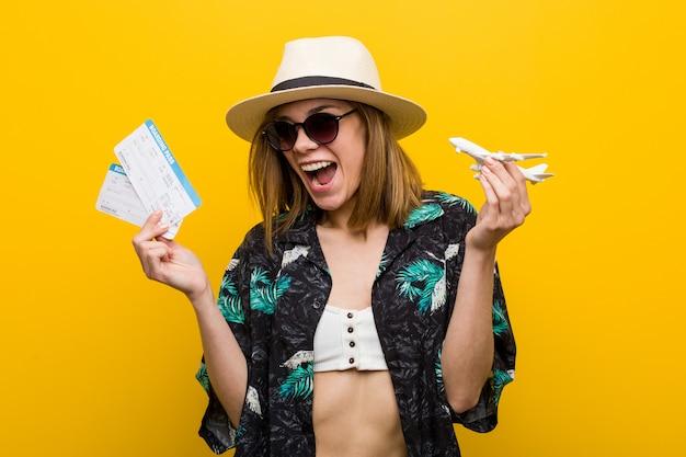 Mulher caucasiano nova que mantém bilhetes de ar muito felizes. Foto Premium