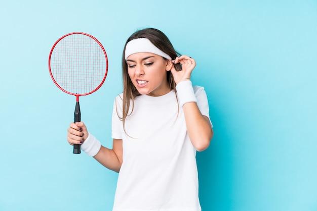 Mulher caucasic nova que joga o badminton isolado cobrindo as orelhas com as mãos. Foto Premium