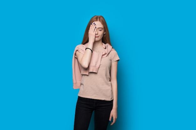 Mulher chateada com cabelo ruivo e sardas gesticulando com a palma da mão no rosto sobre um fundo azul Foto Premium