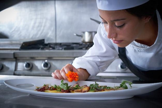 Mulher chef, garnishing, flor, em, prato, em, cozinha Foto Premium