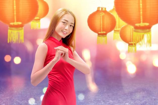 Mulher chinesa asiática em um vestido cheongsam com gesto de parabéns Foto Premium