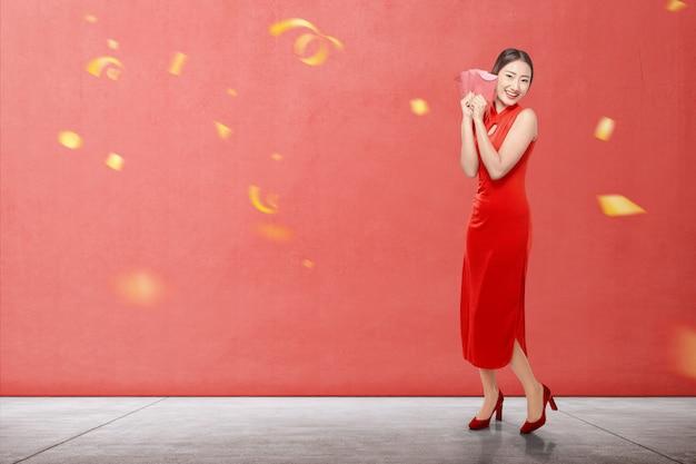 Mulher chinesa asiática em um vestido cheongsam segurando envelopes vermelhos Foto Premium