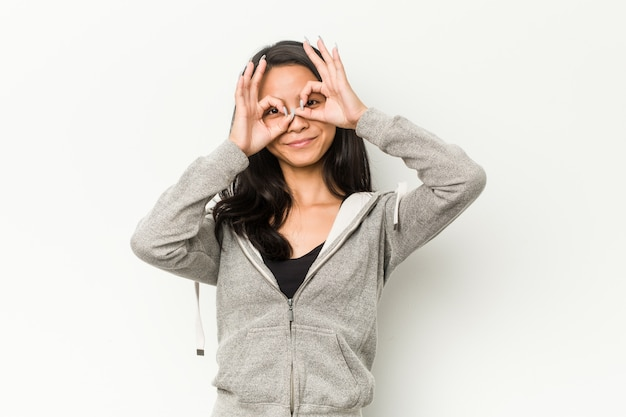 Mulher chinesa de aptidão jovem mostrando sinal bem sobre os olhos Foto Premium