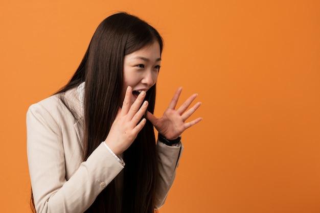 Mulher chinesa de negócios jovem grita alto, mantém os olhos abertos e mãos tensas. Foto Premium