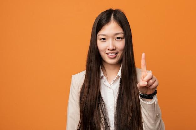 Mulher chinesa do negócio novo que mostra o número um com dedo. Foto Premium