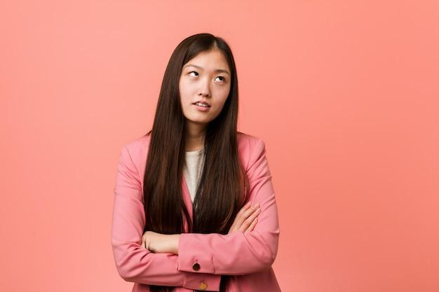 Mulher chinesa do negócio novo que veste o terno cor-de-rosa cansado de uma tarefa repetitiva. Foto Premium