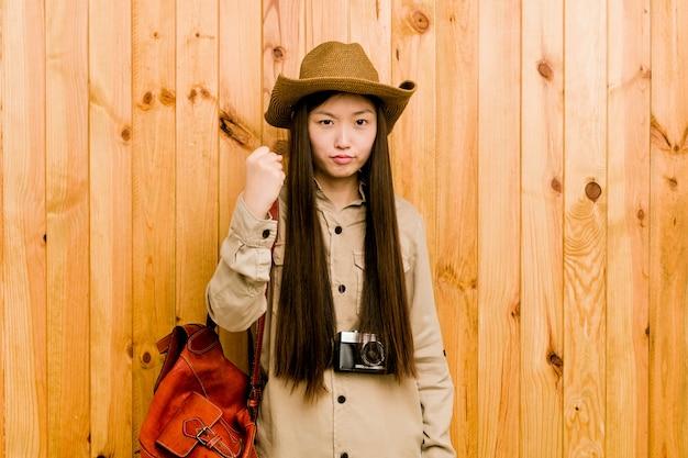 Mulher chinesa nova do viajante que mostra o punho com com expressão facial agressiva. Foto Premium