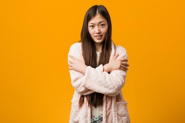 Mulher chinesa nova no frio indo do pijama devido à baixa temperatura ou a uma doença. Foto Premium