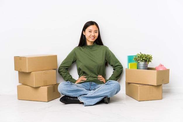 Mulher chinesa nova que move-se para uma casa nova segura mantendo as mãos nos quadris. Foto Premium