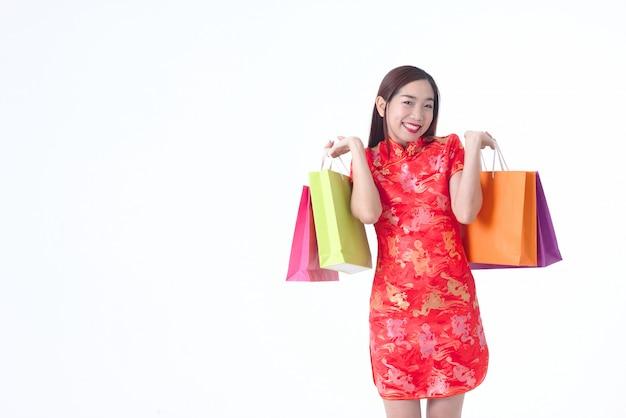 Mulher chinesa que veste o saco de compras vermelho da posse do vestido de cheongsam conceito feliz da compra da mulher. Foto Premium
