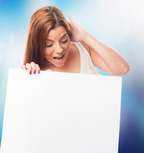Mulher choc que olha a placa branca. Foto gratuita