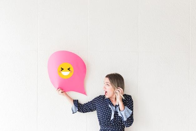 Mulher chocada olhando para papel de bolha do discurso mostrando o ícone rindo Foto gratuita