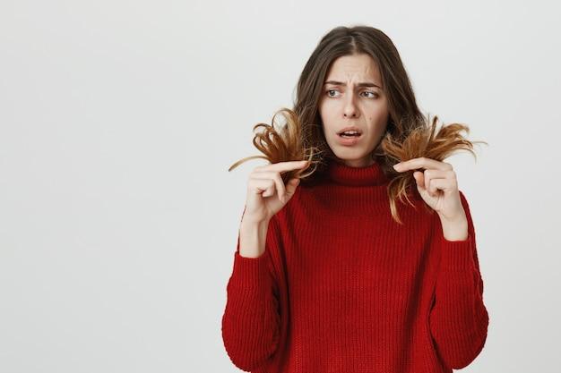 Mulher chocada olhando para pontas duplas, precisa de cabeleireiro Foto gratuita