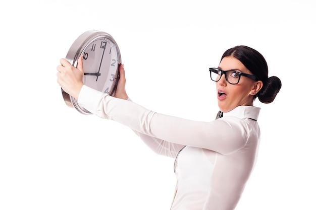 Mulher chocada segurando um relógio de escritório Foto gratuita