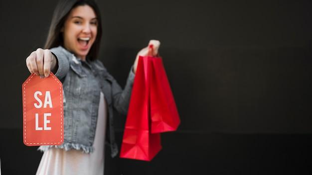 Mulher chorando com pacotes de compras e tablet de venda Foto gratuita