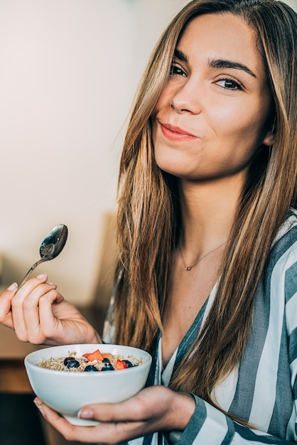 Mulher, cima, comer, aveia, e, frutas, tigela, pequeno almoço Foto Premium