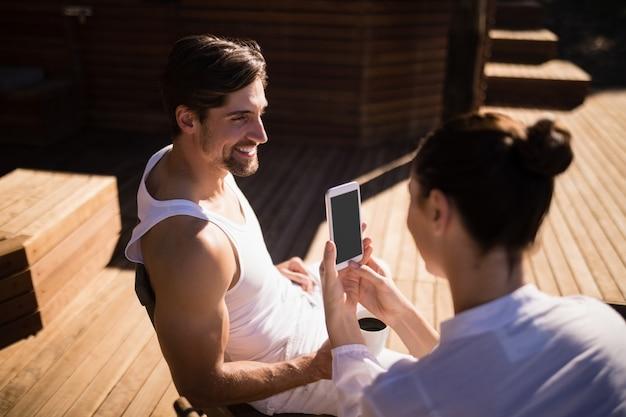 Mulher, clicando, foto, de, homem, com, telefone móvel Foto gratuita