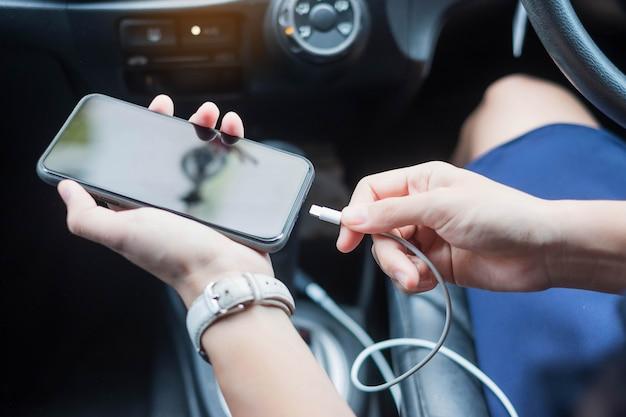 Mulher cobrando smartphone no carro. Foto Premium