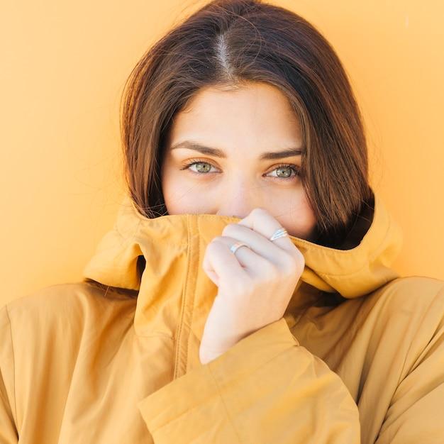 Mulher cobrindo a boca com jaqueta, olhando para a câmera Foto gratuita