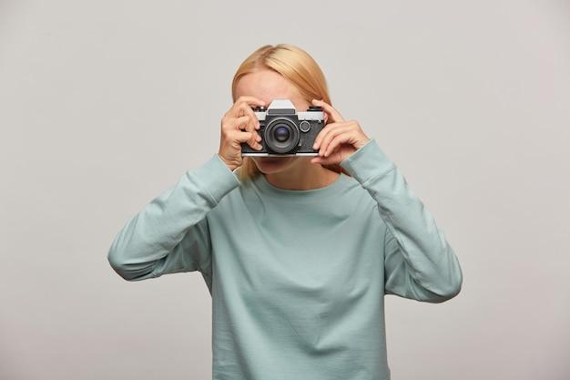 Mulher cobrindo o rosto com a câmera fazendo uma sessão de fotos Foto gratuita