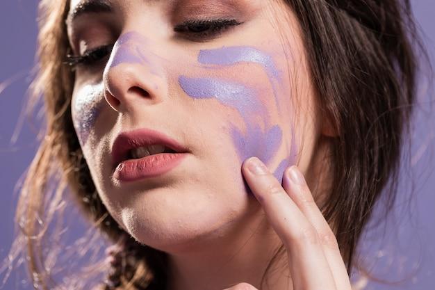 Mulher, cobrindo-se com tinta como um sinal de triunfo Foto gratuita