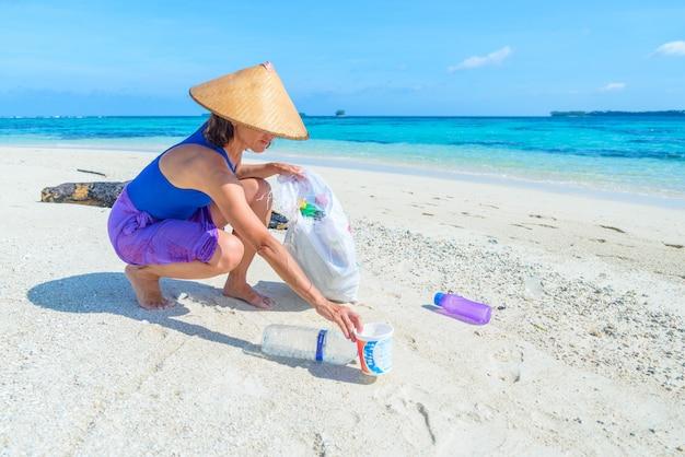 Mulher, colecionar, plástico, garrafas, ligado, bonito, tropicais, praia, mar turquesa Foto Premium