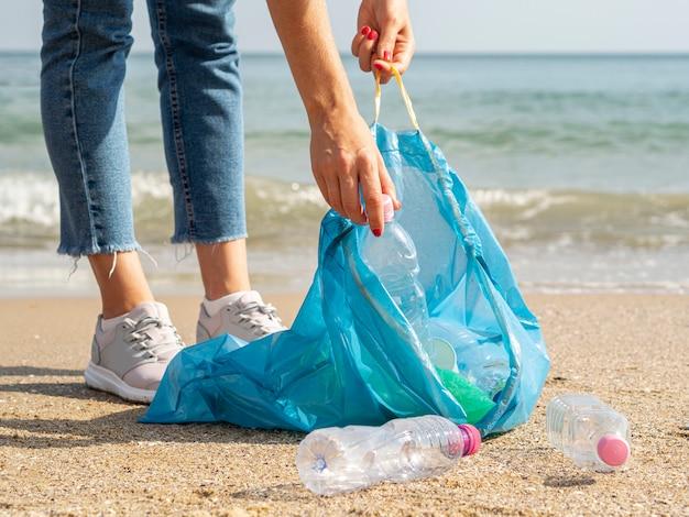 Mulher coletando garrafa de plástico reciclável no lixo Foto gratuita