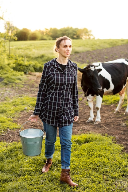 Mulher coletando leite de vaca Foto Premium