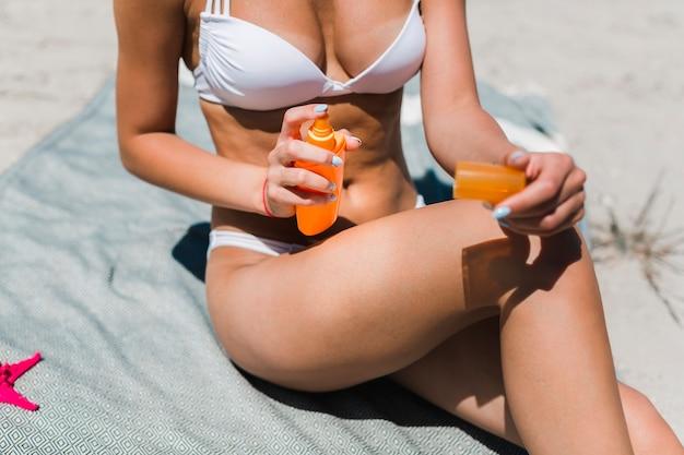 Mulher colheita, aplicando lotion suntan, ligado, perna Foto gratuita