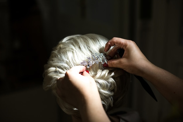 Mulher coloca hairpin de cristal no cabelo loiro da noiva Foto gratuita
