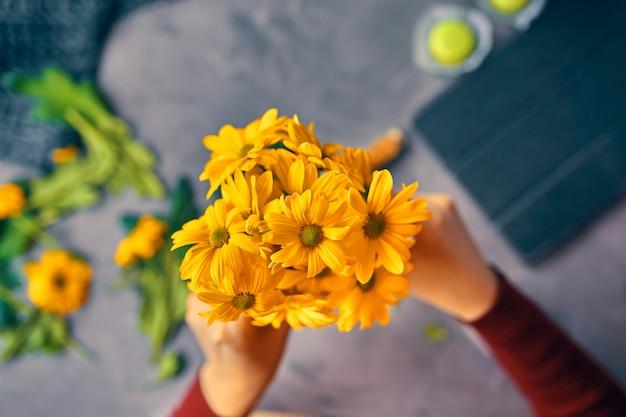 Mulher coloca um crisântemo amarelo flores em um vaso de vidro transparente na mesa loft Foto Premium