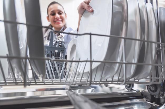 Mulher colocando a louça na máquina de lavar louça na cozinha do apartamento dela Foto Premium