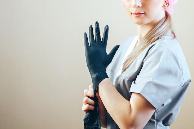 Mulher colocando em luvas de borracha preta, ela em traje cinza corpo e cuidados de saúde Foto Premium
