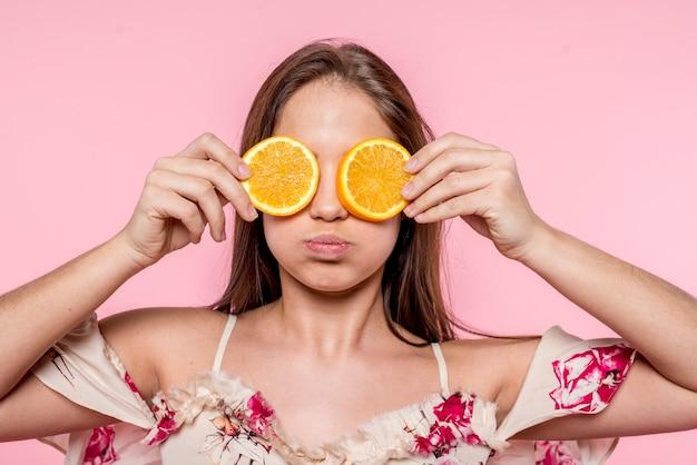 Mulher colocando laranja fatiada para os olhos e se divertindo Foto gratuita