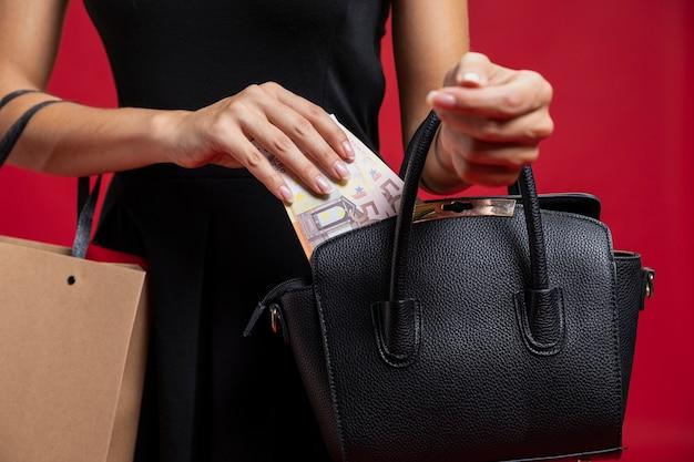 Mulher colocando seu dinheiro na bolsa Foto gratuita