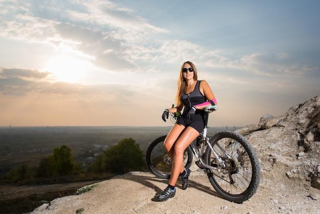 Mulher, com, a, bicicleta montanha, ligado, a, penhasco rocha, sob, um, céu, em, pôr do sol Foto Premium