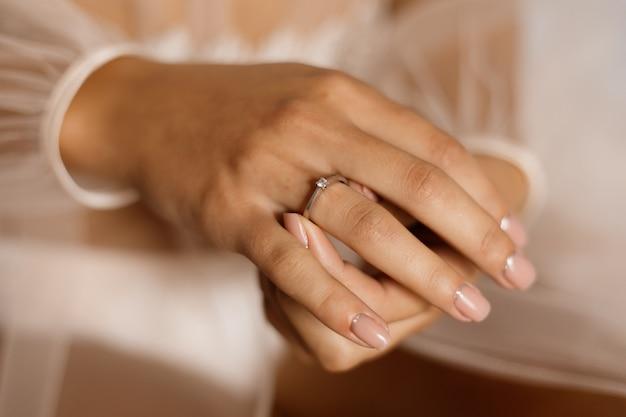 Mulher com anel de noivado com diamante e bela manicure Foto gratuita
