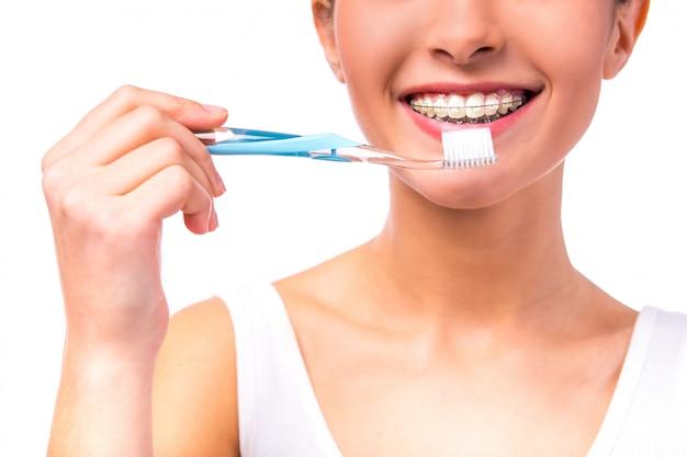 Mulher com aparelho nos dentes, limpa os dentes com escova de dentes. Foto Premium