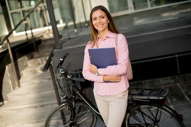 Mulher com arquivos nas mãos em pé ao ar livre na frente da bicicleta elétrica Foto Premium