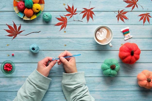 Mulher com as mãos de tricô de crochê. vista superior com bolas de lã, feixes de lã, abóboras de outono decorativas e folhas de outono. Foto Premium