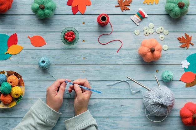 Mulher com as mãos de tricô de crochê. vista superior da mesa de madeira com bolas de lã, feixes de lã, abóboras decorativas, folhas de outono. Foto Premium