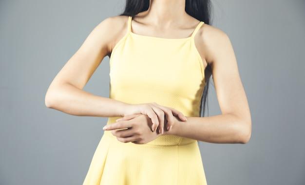 Mulher com as mãos doloridas no cinza Foto Premium