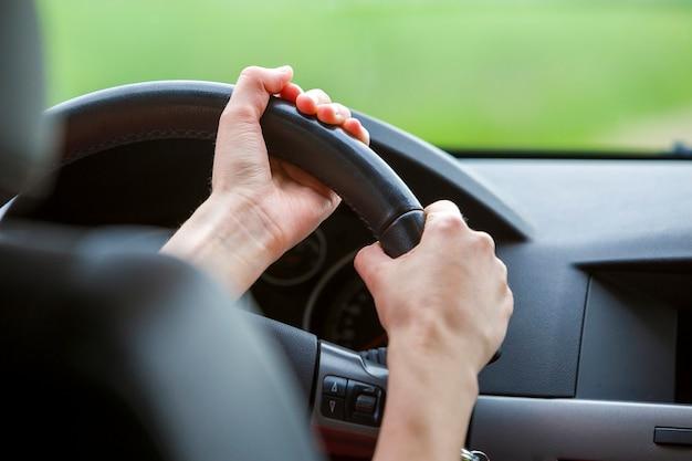 Mulher com as mãos no volante dirigindo um carro. Foto Premium